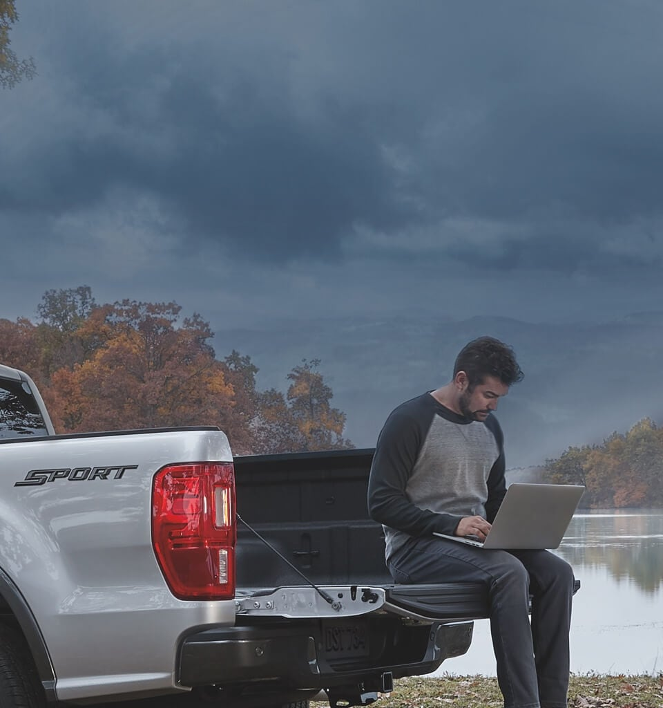 Man using laptop while sitting on truck bed of 2020 Ford Ranger Lariat parked near lake