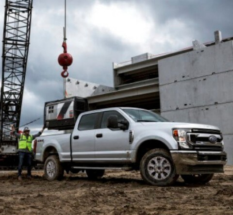 Construction workers near 2020 Ford Transit in White Platinum with open rear doors at work site