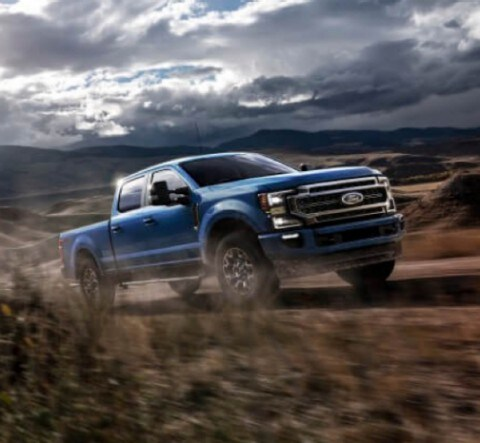 2020 Ford Super Duty Crew Cab in Velocity Blue being driven uphill on dirt road in desert